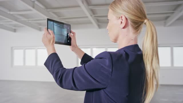 stockvideo's en b-roll-footage met vrouwelijke makelaar die foto's maakt van een kantoorruimte in een leeg bedrijfsgebouw met behulp van een digitale tablet - paardenstaart haar naar achteren