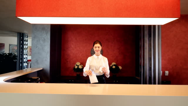 Female receptionist smiling and giving key card at hotel lobby.