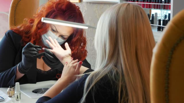 female red makes a spa procedure for the fingernails of the client - pesche bambino video stock e b–roll