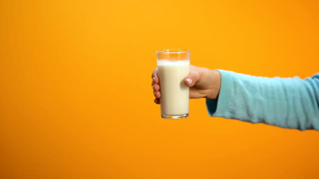 Female refusing to drink milk showing stop gesture on bright background, health video