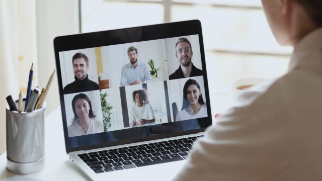 Female remote worker video calling colleagues working from home office