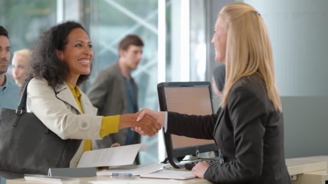 Female rental clerk giving the car keys to a female customer renting a car video