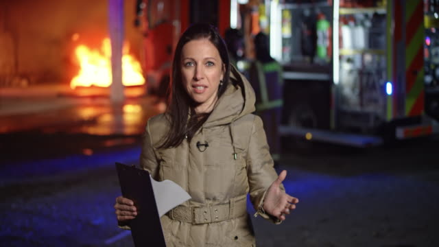 Female reporter reporting from the scene of the fire seen in the background video