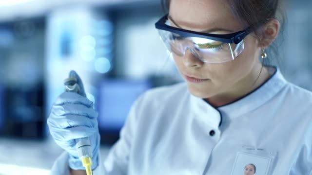 女性研究員は、大きな近代的な研究室のピペット充填テスト チューブを使用します。背景科学者の作業しています。 - 科学研究点の映像素材/bロール