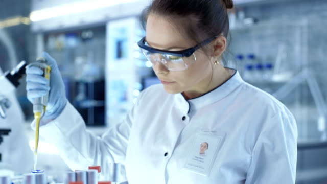 female research scientist uses micropipette filling test tubes in a big modern laboratory. in the background scientists are working. - chemistry stock videos and b-roll footage