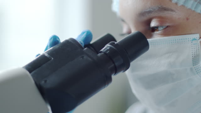 female researcher in mask and gloves using microscope and posing for camera - covid testing стоковые видео и кадры b-roll