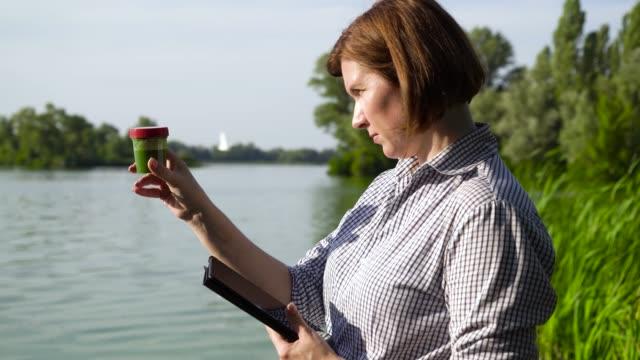 forscherin mit tablette untersucht probe von flusswasser mit grünalgen - überprüfung stock-videos und b-roll-filmmaterial
