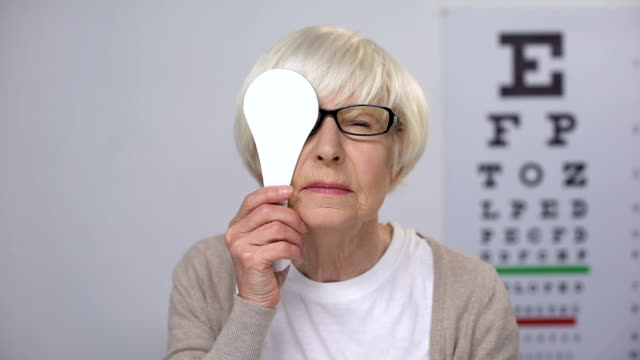 Female retiree in glasses closing eye and shaking head, age related diseases Female retiree in glasses closing eye and shaking head, age related diseases eye chart stock videos & royalty-free footage