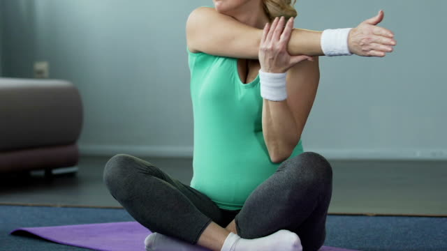 Female retiree sitting on fitness mat and warming up by stretching arms, workout video