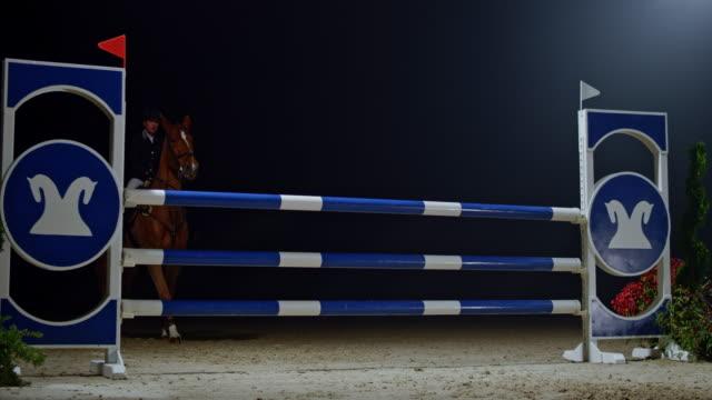 slo mo kvinna ryttare på hennes kastanj häst hoppa en järnväg på natten - häst tävling bildbanksvideor och videomaterial från bakom kulisserna