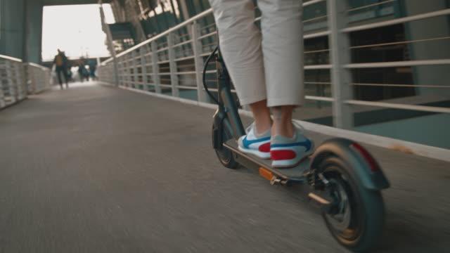 female riding electric push scooter on footbridge - monopattino elettrico video stock e b–roll