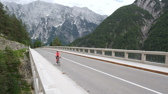 AERIAL Female road cyclist riding across a bridge overlooking the mountains