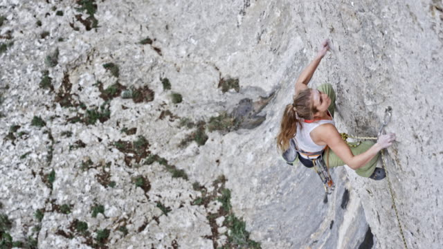 SLO MO Female rock climber letting go while high in the rock wall video