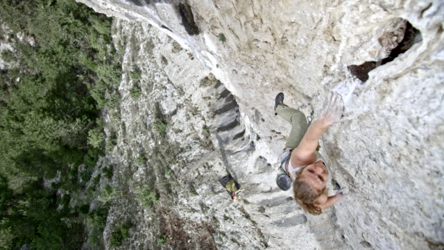 SLO MO Female rock climber letting herself go while failing to get a grip in the cliff
