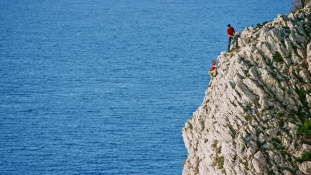vídeos y material grabado en eventos de stock de escalador de roca ld mujer llegar a la cima del acantilado irregular sobre el mar y su compañero la felicita - escalada en rocas