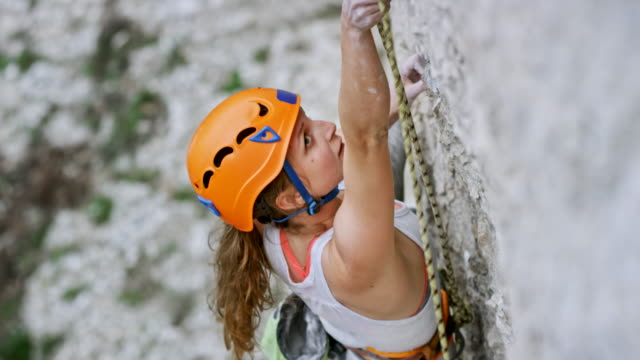 Female rock climber securing herself as she climbs up the cliff Medium handheld shot of a female climber securing herself while ascending the cliff with an orange helmet on her head. Shot in Croatia. recreational pursuit stock videos & royalty-free footage
