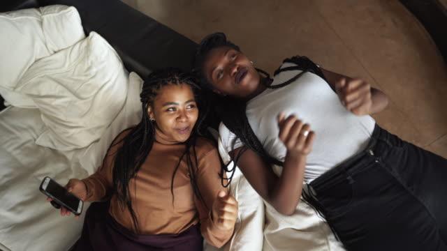 vídeos y material grabado en eventos de stock de compañeras de cuarto femeninas tumbada en el sofá y hablando y bailando - actividades recreativas