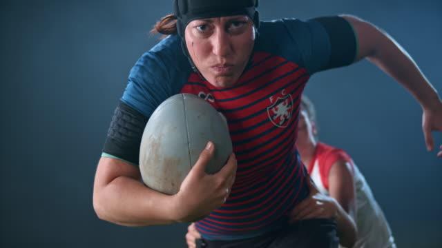 slo mo 여성 럭비 선수가 공을 잡고 상대를 능가 - 헌신 스톡 비디오 및 b-롤 화면