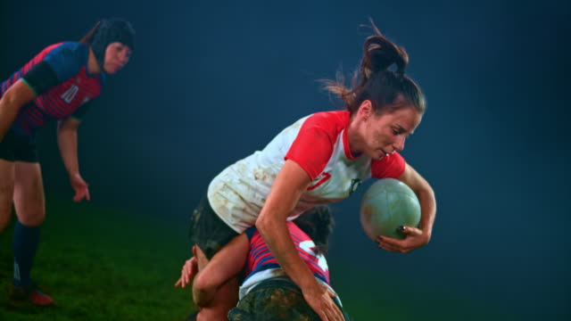 slo mo female rugby player pushing her opponents away but being tackled to the ground - trykot filmów i materiałów b-roll