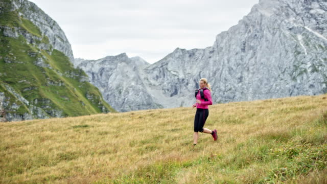 DS Female runner descending a mountain down a grassy meadow on a sunny day Wide dolly shot of a female runner descending a mountain across a grassy meadow with a beautiful view in sunshine. Shot in Slovenia. pedal pushers stock videos & royalty-free footage