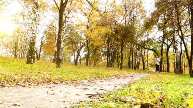 Female runner jogging in autumn park forest with fall colors video