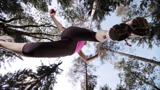 SLO MO Female runner making a jump below the tree tops video