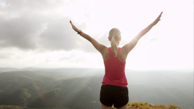 TS SLO MO female runner reaching the top Slow motion tracking shot of a woman running towards the edge on the mountain, stopping and raising her hands. She is very happy she reached her goal. mid adult stock videos & royalty-free footage