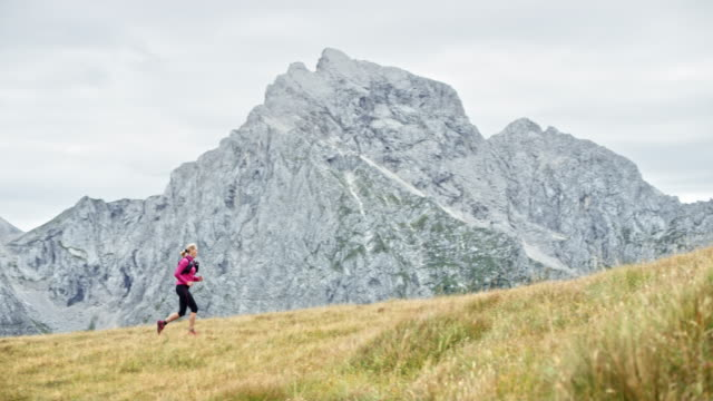 DS Female runner running across a grassy mountain ridge overlooking the nearby mountain peaks Wide dolly shot of a female runner running across a grassy mountain ridge with a beautiful view of the nearby mountains. Shot in Slovenia. pedal pushers stock videos & royalty-free footage