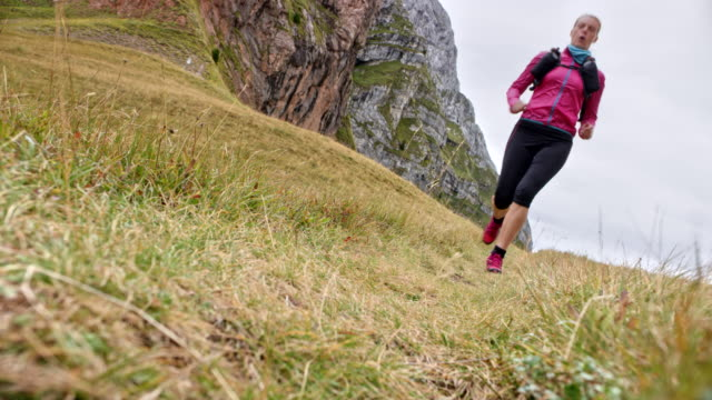ld female runner running across a mountain meadow - pantaloni capri video stock e b–roll