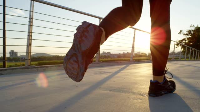 vídeos de stock, filmes e b-roll de câmera lenta: feminino corredor cruza ponte em cidade em mágico sol nascente - fazendo cooper