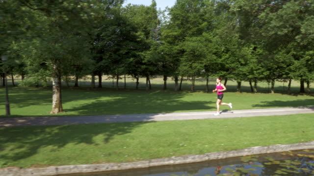 vidéos et rushes de vue aérienne de coureur de femme jogging sur un lac de soleil - joggeuse