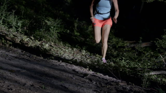 SLO MO Female runner running in forest at night video