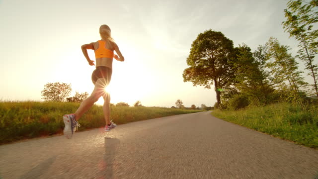 SLO MO TS Female runner running into sunset in countryside video