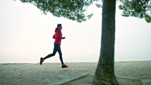 SLO MO TS Female runner running on a footpath along the beach on a foggy morning