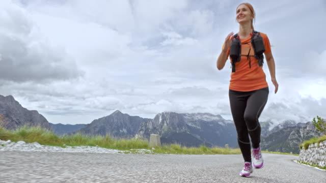 vídeos y material grabado en eventos de stock de slo mo mujer corredor corriendo por una carretera de montaña en un día nublado - sudadera