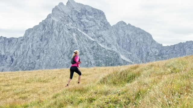 DS Female runner running up the meadow high in the mountains on a sunny day Wide dolly shot of a woman running up a meadow high in the mountains in sunshine. Shot in Slovenia. pedal pushers stock videos & royalty-free footage