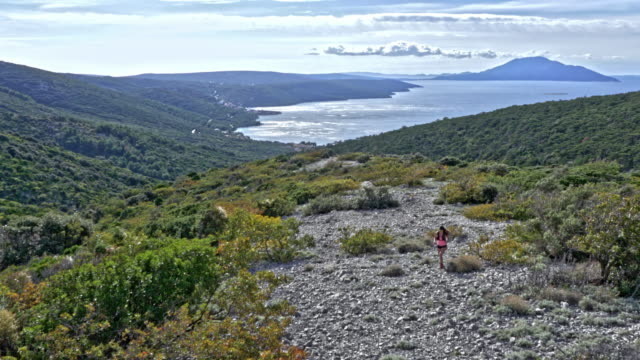 AERIAL Female runner running up the rocky mountain on a trail overlooking the Adriatic sea with nearby islands video
