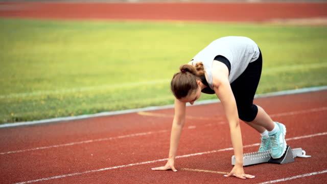 Female runner starting at stadium video