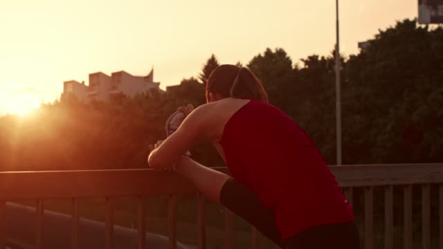 SLO MO Female runner stretching her leg at sunset video