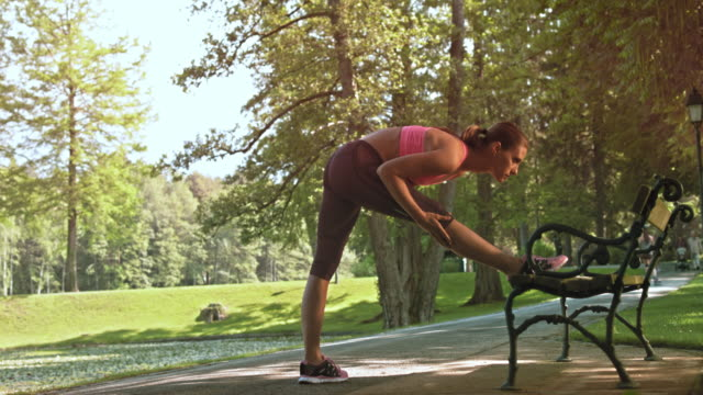 DS Female runner stretching her legs on a park bench video