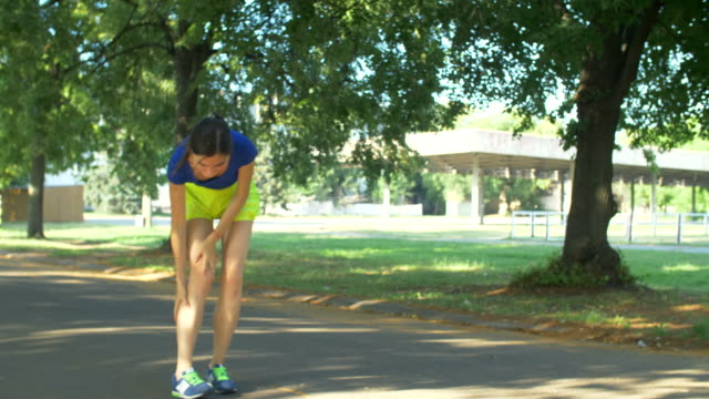 Female runner touching twisted ankle in pain Beautiful fit female runner touching foot in pain, has sprained and strained ankle during jogging in public park. Sporty fit woman experiencing typical road running problem twisted ankle. ankle stock videos & royalty-free footage