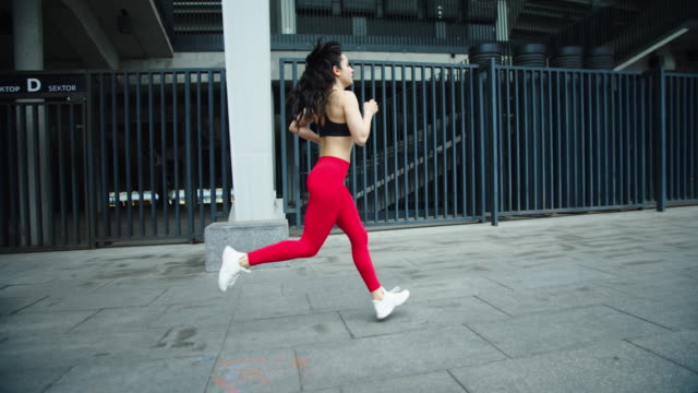 vídeos de stock e filmes b-roll de female runner training outdoor in slow motion. fitness woman running on street - young woman running city