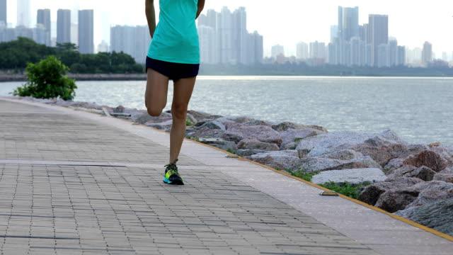 female runner warming up and running on seaside - rozgrzewka filmów i materiałów b-roll