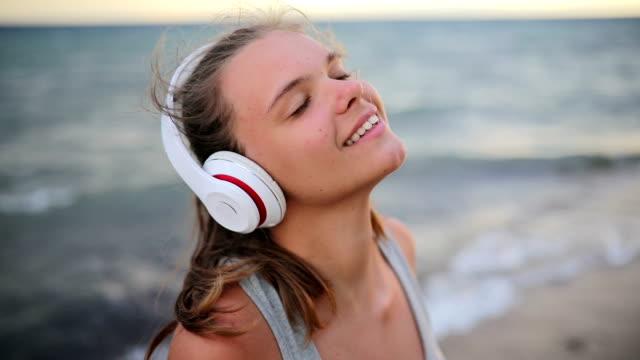 vídeos y material grabado en eventos de stock de corredor de la mujer con auriculares y brazo banda de deporte escuchando música en pausa - escuchar