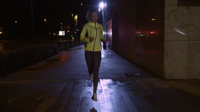 SLO MO TS Female running along a rainy street at night Slow motion wide tracking shot of a woman in a yellow jacket running along a city street at night. front view stock videos & royalty-free footage