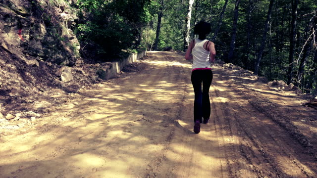 Female running, jogging on rural road, back view steadicam shot Female running, jogging on rural road, back view steadicam shot human back stock videos & royalty-free footage