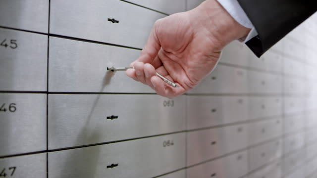 Female safe deposit box clerk unlocking the safe box for a customer granting him access to his valuables video