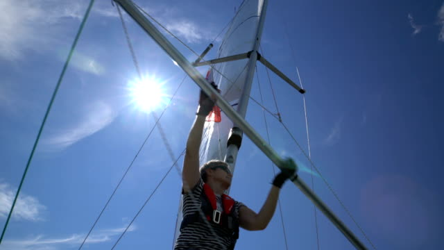 A female sailor changes the Spinnaker on the bow of the yacht. A female sailor changes the Spinnaker on the bow of the yacht. mast sailing stock videos & royalty-free footage