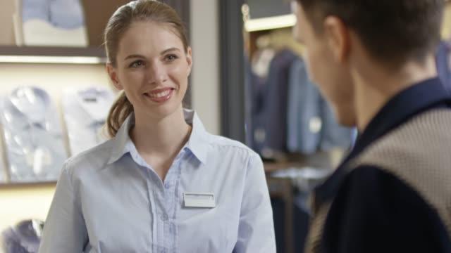 female sales assistant helping customer - ассистент стоковые видео и кадры b-roll