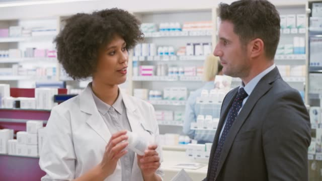 Female salesperson at the drugstore advising a business man about a vitamin supplement